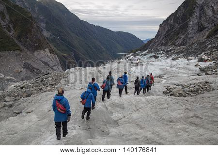 Franz Josef, New Zealand - March 22, 2015: A group of tourists hiking towards a helicopter on Franz Josef Glacier.
