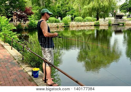 Sandwich Massachusetts- July 13 2015: Local resident fishing in the mill pond by the Dexter Grist Mill on a quiet Summer afternoon