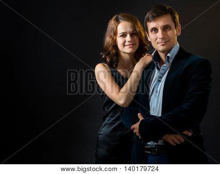The Russian girl in black skin-tight dress hugging a guy in a velvet jacket