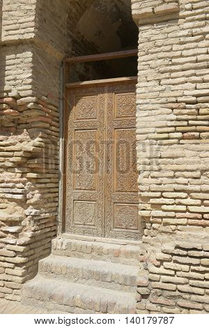 Woodcarving. The old door is locked. National Samarkand patterns.