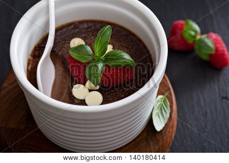 Chocolate pudding with raspberries and basil baked in ramekins poster