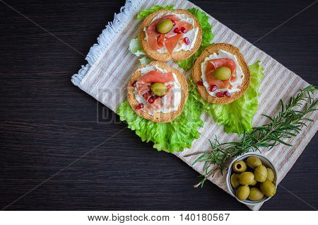 Delicious bruschetta with prosciutto, olives and pomegranate on dark background with rosemary. Italian bruschetta sandwich. Italian appetizer. Top view.
