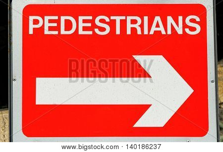Red pedestrians direction sign pointing to the right