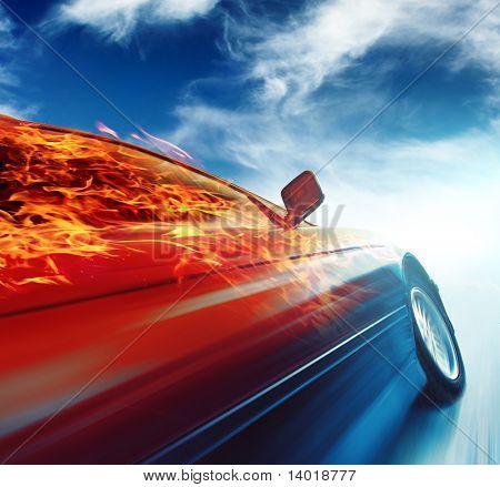 Burning car in motion over blue sky background