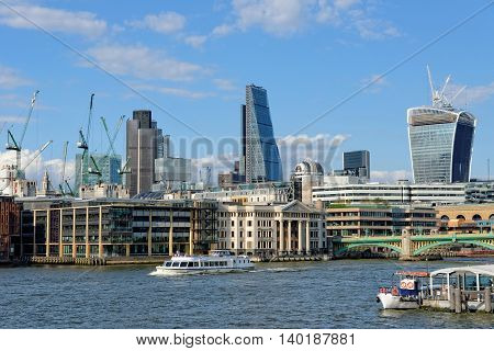 LONDON UNITED KINGDOM - JULY 1 2014: A City Cruises tour boat sails on the Thames River near Southwark Bridge. Thames is the longest river in England with 346 km (215 miles) long.