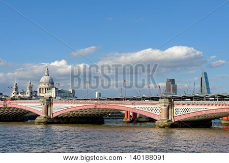 LONDON UK - JULY 1 2014: A view of Blackfriars bridge - a road and foot traffic bridge over the river Thames against a background of St Paul Cathedral the City and the Blackfriars railway bridge.