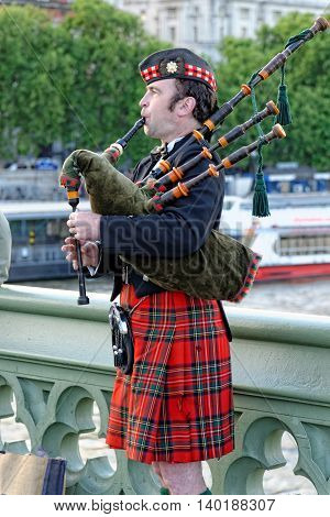 LONDON UK - JULY 1 2014: Bagpiper musician on Westminster Bridge in a traditional Scottish costume.