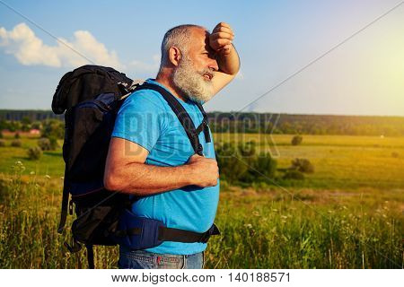 Side view of fit aged man with rucksack standing in the field and wiping his forehead on warm sunny day