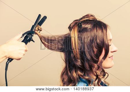 Professional straighten hair in salon. Young girl care about her hairstyle