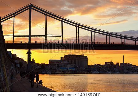 KIEV UKRAINE - JULY 22 2016: Breathtaking sunset over Trukhaniv bridge in Kiev. People enjoying the scene.