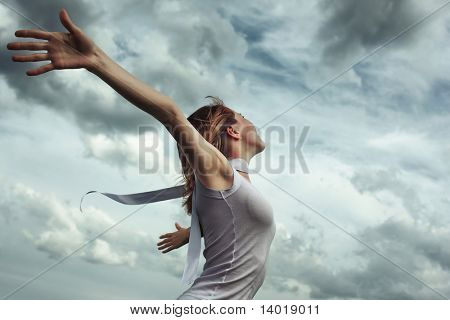 Young woman in white shirt with raised hands over stormy cloudscape