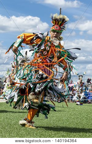 Coeur d'Alene Idaho USA - 07-23-2016. Colorfully dressed young man at powwow. Young dancer participates in the Julyamsh Powwow on July 23 2016 at the Kootenai County Fairgrounds in Coeur d'Alene Idaho.