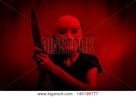 Mysterious woman in black dress wearing white mask holding knife ,Scary background for halloween