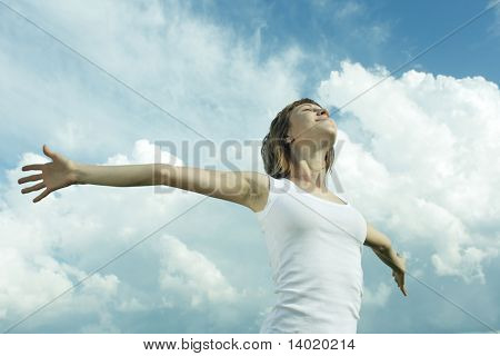 Young woman with raised hands and fluffy sky background