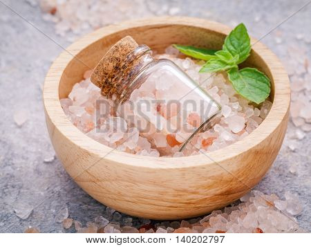 Closeup Himalayan Pink Salt In Wooden Bowl And Bottle  With Peppermint Leaves On Stone Background. H