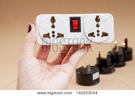 Plug socket in hand with the background of universal adaptor set
