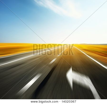 Blurred asphalt road with signs and blue sky