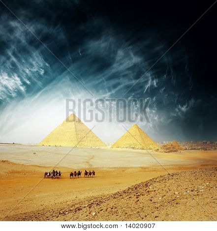 Grate Giza pyramids and group of riders on camels. Egypt