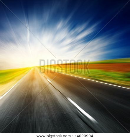 Blurred asphalt road and blue sky with clouds and light