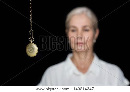 Woman being hypnotized with pendulum against black background