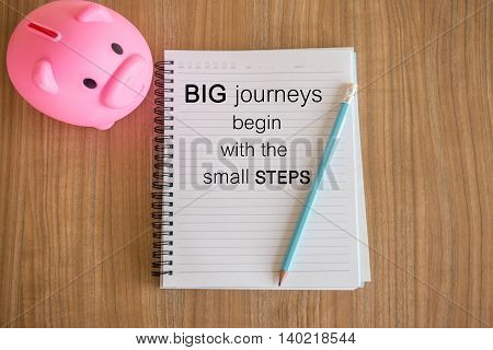 Word  Big Journeys Begin With The Small Steps.inspirational Motivational Quote On Paper And A Piggy