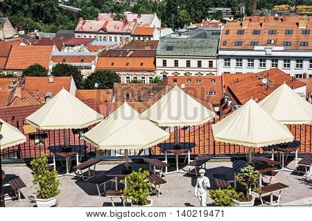 Empty tables chairs and umbrellas in the garden restaurant Trencin city Slovak republic. Red roofs. Urban scene.