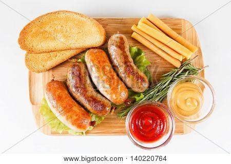 October fest traditional menu beer and roast beef or chicken sausage with ketchup mustard and rosemary. Wooden cutting board