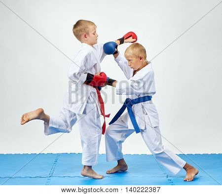 With blue and red overlays on his hands athletes train paired exercises karate
