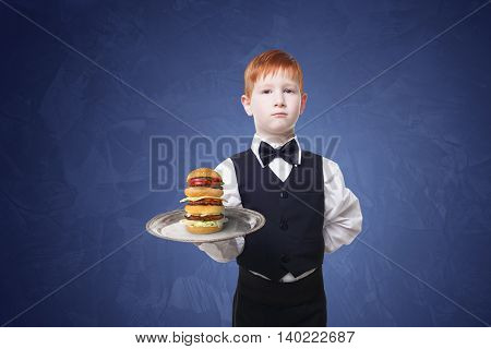 Little waiter stands with tray serving big double hamburger. Redhead Child boy in suit plays restaurant servant, gives burger at blue background