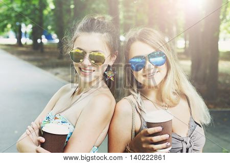 Two beautiful young boho chic stylish girls portrait in park. Happy smiling friends couple in colored sunglasses, having fun outdoors. Attractive young women drink coffee in summer city, youth fashion