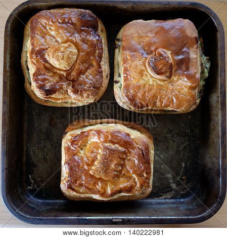 Savoury meat or vegetable pies on an old baking tray. Photographed in New Zealand NZ.