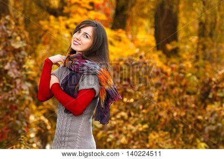 Portrait of beautiful smiling young woman in autumn park. Smiling happy girl portrait in autumn. Concept autumn. Girl on autumn park background