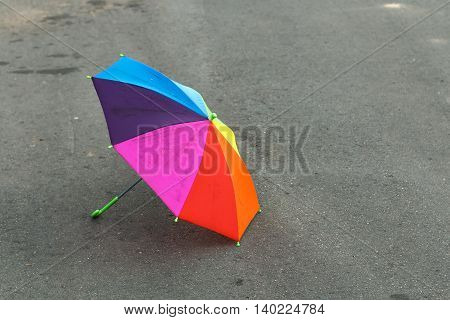 Rainbow umbrella lying on the pavement after the summer rain, forgotten by a child. Sadness and loneliness