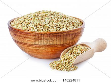 Green buckwheat in clay bowl and wooden scoop isolated on a white background. Healthy food. Healthy groats