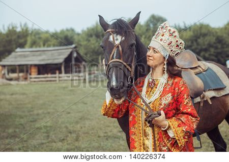 Medieval Noblewoman In Red Dress And Jewelry Is Going To A Horse Ride.