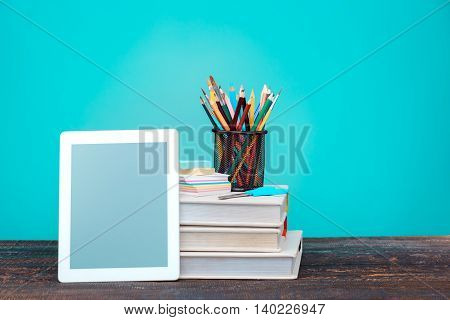 Back to School concept.School Books, colored pencils and laptop on blue background