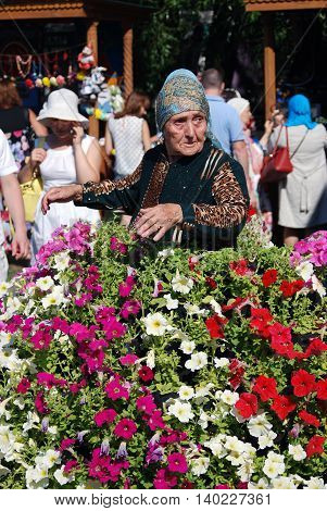 MOSCOW - JULY 17 2016: Senior woman surrounded by flowers. Sabantui celebration in Moscow in Kolomenskoye park. Sabantui is a national Tatar and Bashkir festival celebration of end of spring field work.
