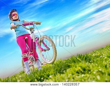 Bicycling child. Girl rides bicycle. Little girl in bicycling. Bicycling is good for child health. Cyclist look away on blue sky with clouds.
