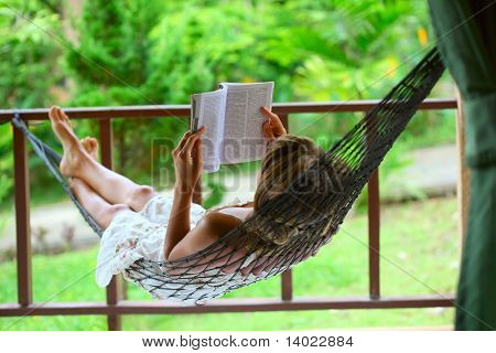 Young woman reading a book lying in hammock