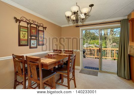 Viwe Of Wooden Table Set In The Dining Room With Mocha Walls.