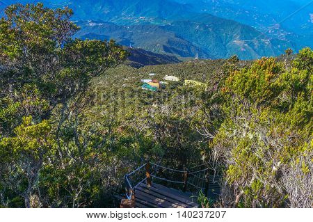 Laban Rata seen through twisted alpine trees growing at high altitude from Mountain Kinabalu.Laban Rata offers climbers warm lodgings & hot meals before & after climbing to the peak of Mount Kinabalu.