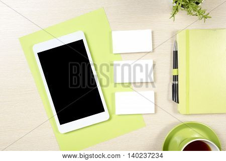 Business card blank, smartphone or tablet pc, flower, coffee cup and notepad, pen at office desk table top view. Corporate stationery branding mock-up.