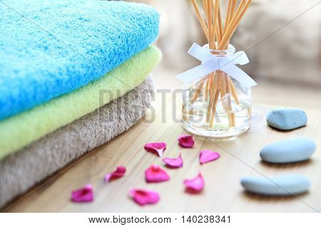 Aromatherapy reed difuser bottle on a wooden table with towels petals and massage stones poster