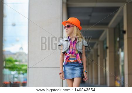 Portrait of girl in fashionable clothes. Elegant Charming cute little girl in sunglasses orange hat. Adorable happy child walking in big mall along the window displays and looking. Shopping in big store.