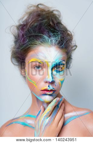 Painted beautiful woman face, artistic make up face art, close up. beauty fashion style in red, yellow, blue colors.