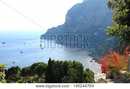 Capri island in summer. Tyrrhenian sea with yachts and boats on clear day. Italy, Europe.