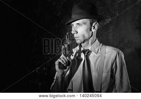 Handsome detective in trench coat holding a gun in the dark. Noir film style. Black and white photography