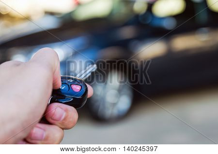Car remote control in hand man with copy space blurry car in packing background , Shallow DOF