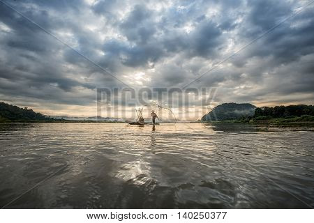 Fisherman On Boat In Action When Fishing Of Fish Trap On Mekong River