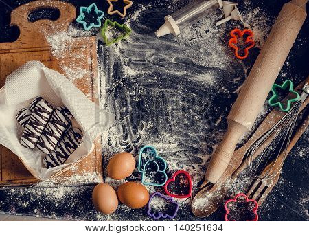 Baking concept on dark background. Baking cookies for children top view of variety of baking utensils with different kind of flour eggs and colorful cutters on black chalkboard. Top view.